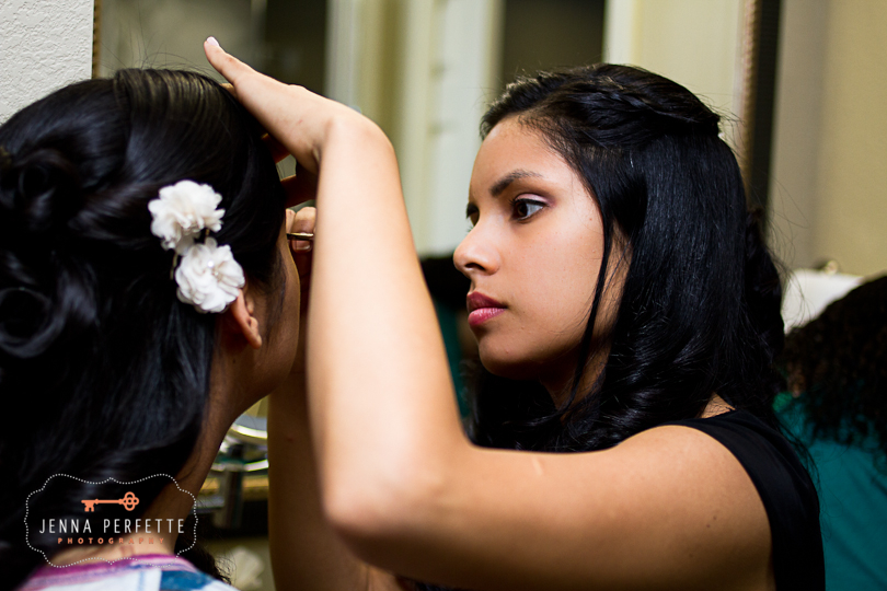 bride puts on makeup with sister bridesmaid