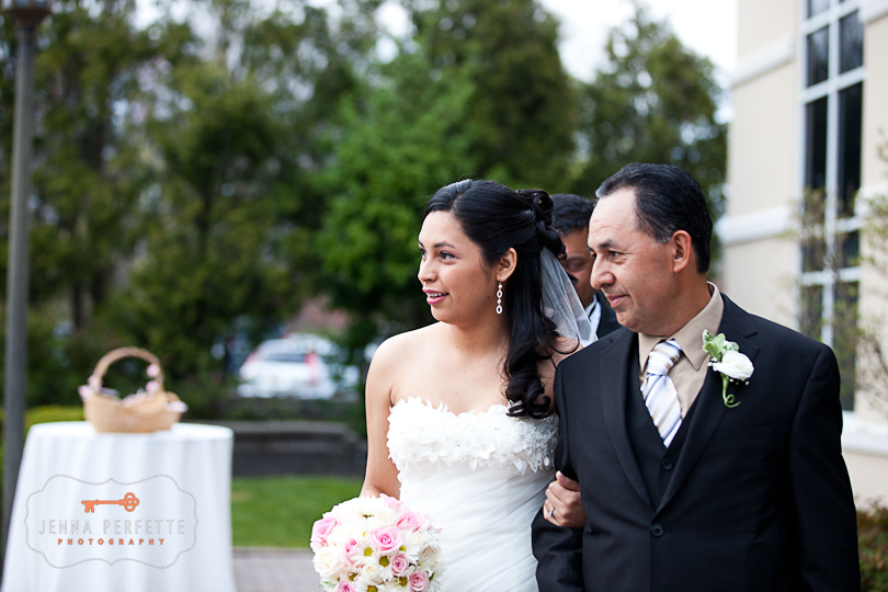 bride walks down the asile with her dad