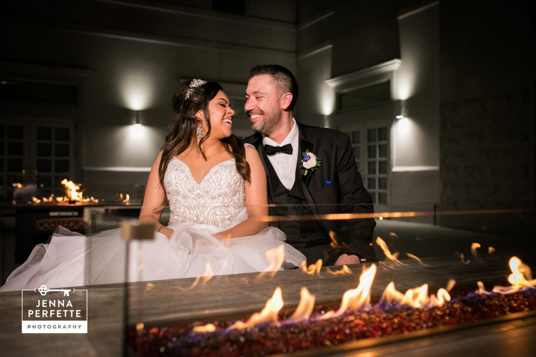 Bride and Groom Sitting In Front of a Fire