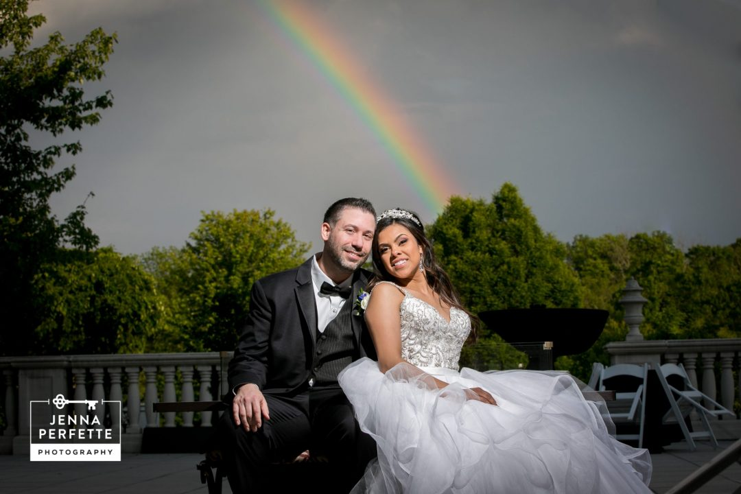 Bride and Groom Sitting Outside with Rainbow in Sky A Refreshing Spring Wedding at The Palace